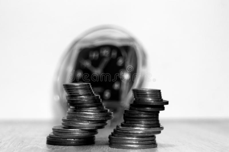 Two uneven piles of coins lies in front of a blurred alarm clock in the background royalty free stock photo