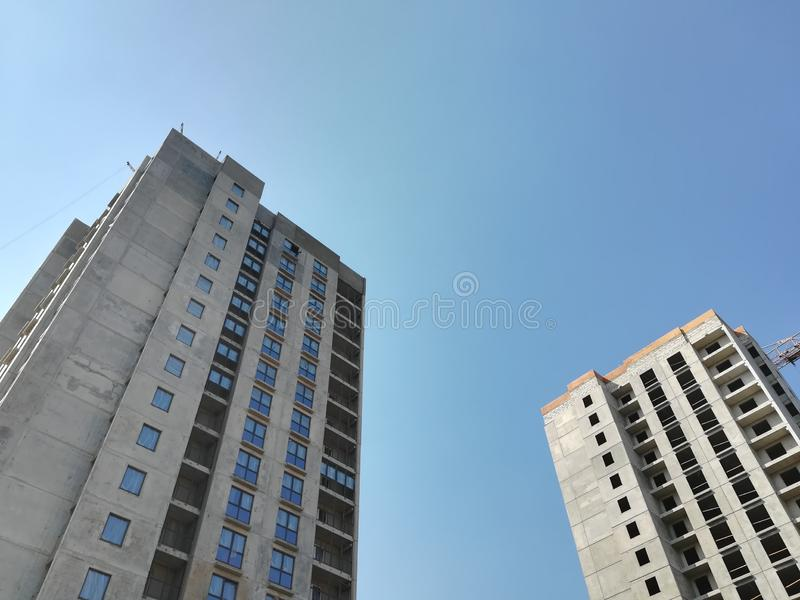 Two unfinished multi-storey residential building on a Sunny day against the blue sky. Empty apartment. Bottom-up view. Construction crane royalty free stock image