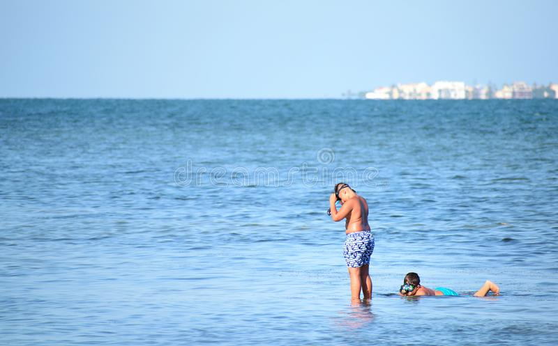 two unidentified children snorkeling on the beach stock photos