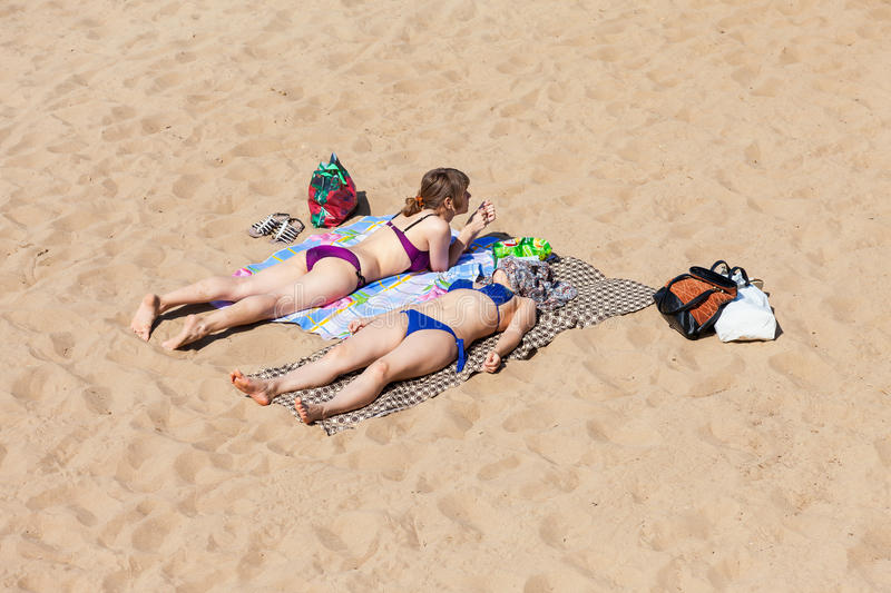 Two unidentified girls sunbathing at the city beach on the shore royalty free stock photo