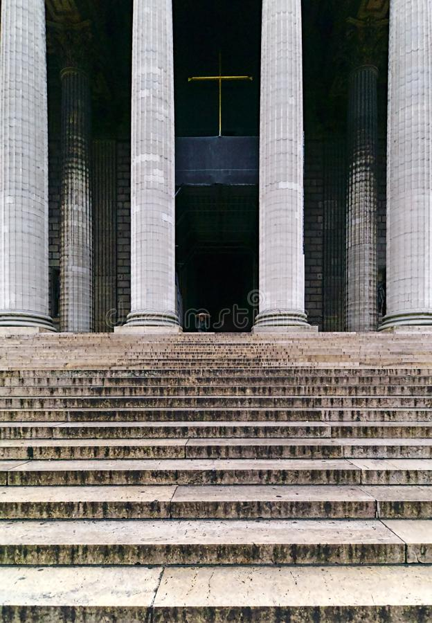 Two unidentified people getting out of the entrance of Madeleine church in Paris. Modern, house, wall, urban, ancient, architecture, dark, religion, stairs stock photography