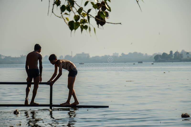 Two unidentified unknown poor slum boys, wearing shorts, playing near Versova beach, Mumbai, Maharashtra, India royalty free stock image