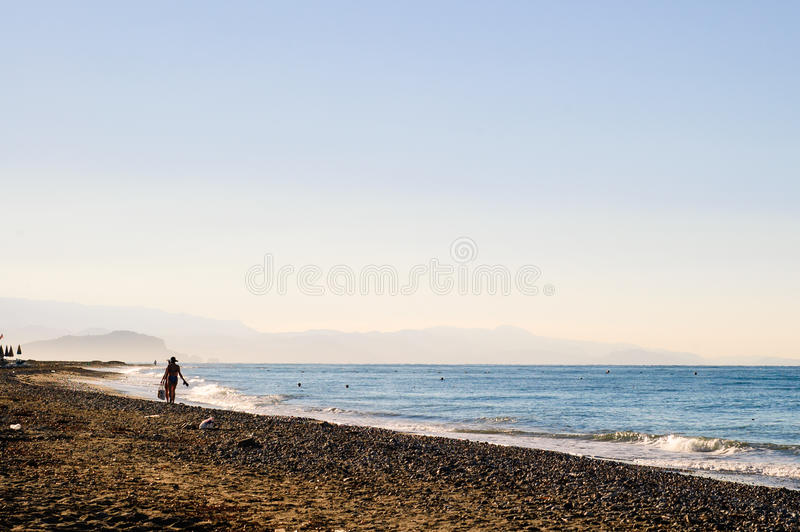 Two unidentified woman walking along the beach royalty free stock image