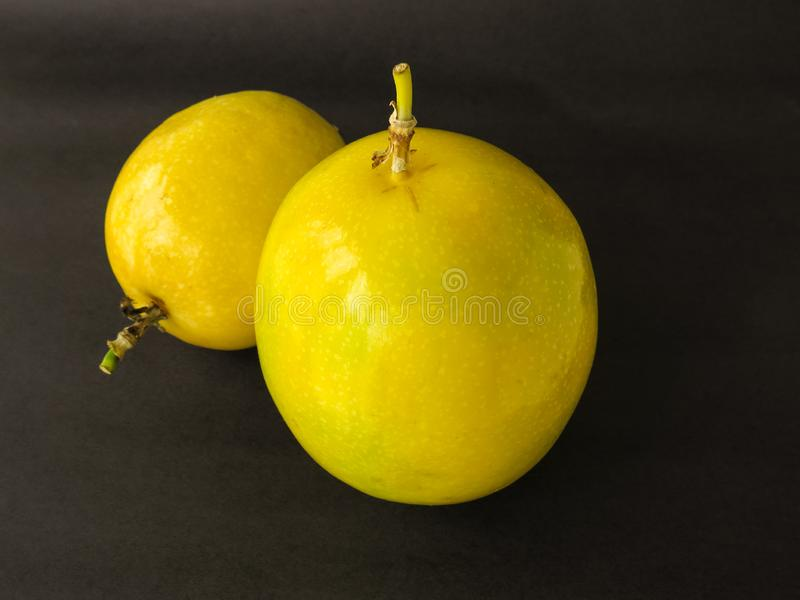 Two units of passion fruit, on black background. Two units of passion fruit, ripe, isolated on black background royalty free stock photography
