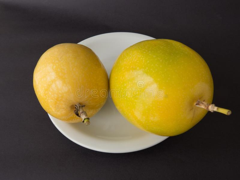 Two units of passion fruit on white plate, on black background. Two units of passion fruit on white plate, ripe, isolated on black background royalty free stock image