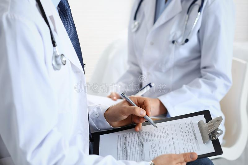 Two unknown doctors filling up medical form on clipboard, just hands closeup. Physicians asking question to patient or royalty free stock photos