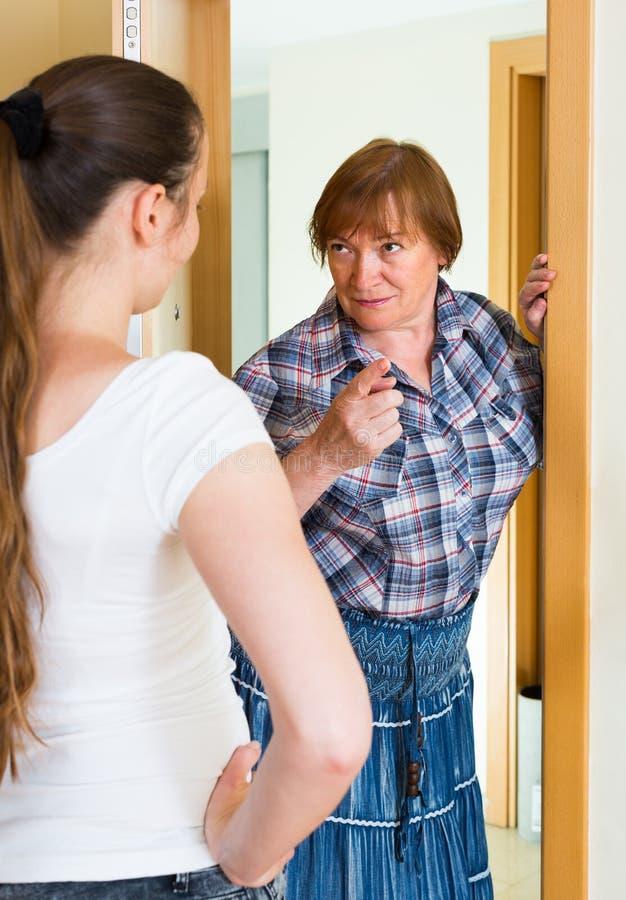 Two unpleased women at doorway. Unpleased senior mature women and adult girl standing at doorway stock image