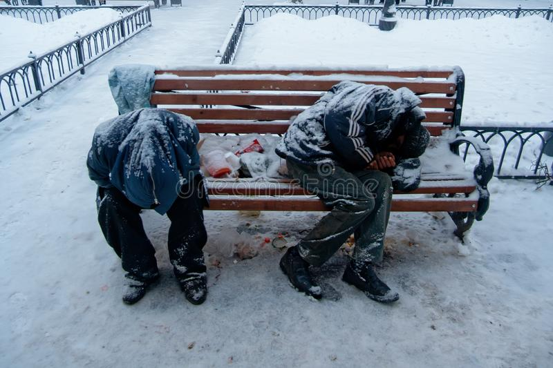 Two unrecognizable dirty homeless men or alcoholics or drug addicts are sleeping on bench in cold winter stock photography