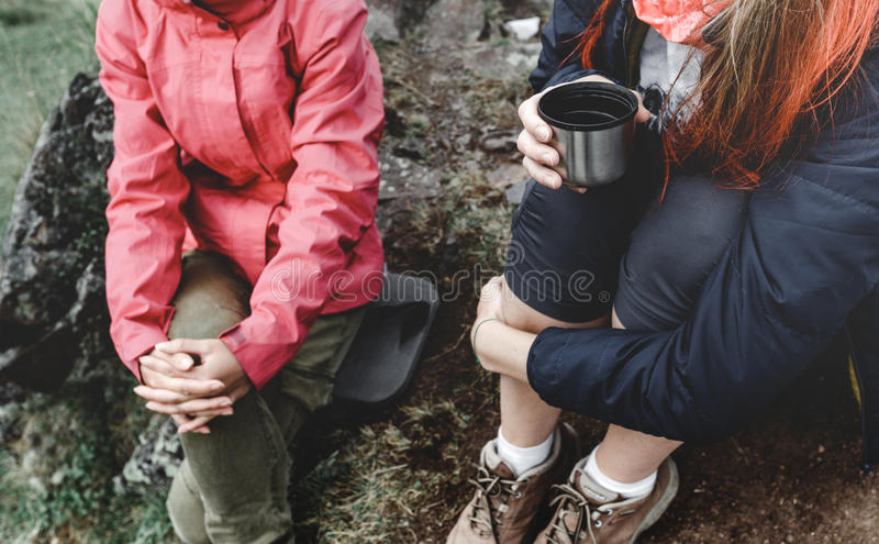 Two Girls Traveler Drink Tea Or Coffee While Relaxing. Hiking Recreation Tourism Concept royalty free stock photography