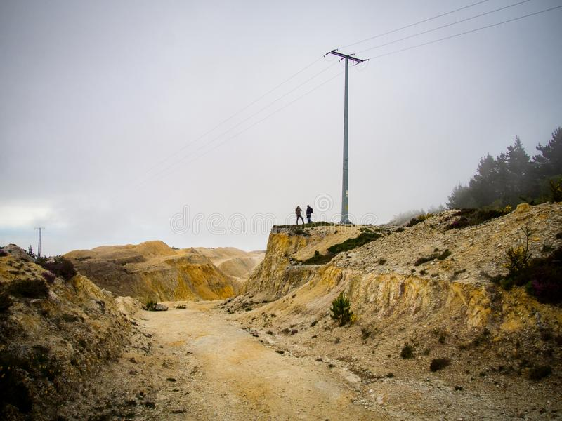 Desolate landscape. Two unrecognizable men in desolate landscape stock image