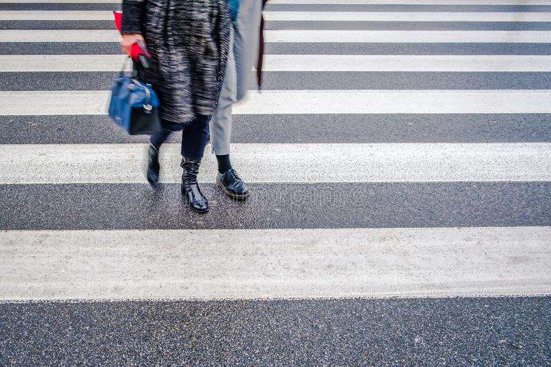 Two unrecognizable persons in black shoes cross wet street after rain on crosswalk, red umbrella, parallel lines royalty free stock image