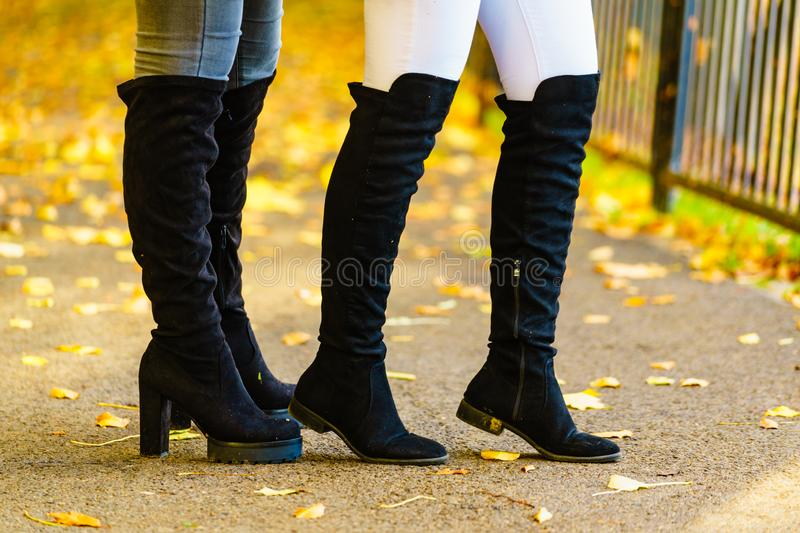 Two women wearing black knee high boots stock photography