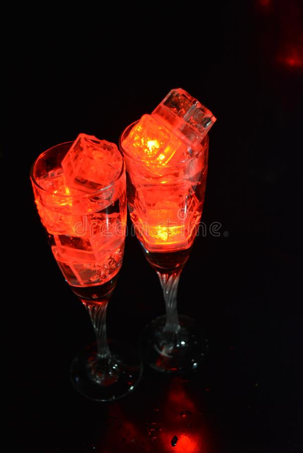 Two unusual glasses of champagne with a drink and bright red ice chips. Original image of love and mysticism in the form of two glasses of champagne with a red royalty free stock photo