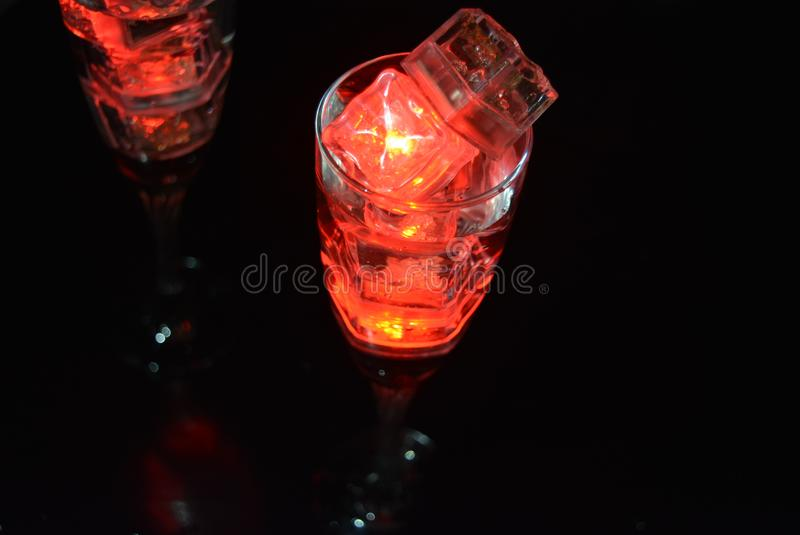 Two unusual glasses of champagne with a drink and bright red ice chips. Original image of love and mysticism in the form of two glasses of champagne with a red stock images