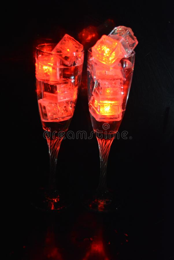 Two unusual glasses of champagne with a drink and bright red ice chips. Original image of love and mysticism in the form of two glasses of champagne with a red royalty free stock images
