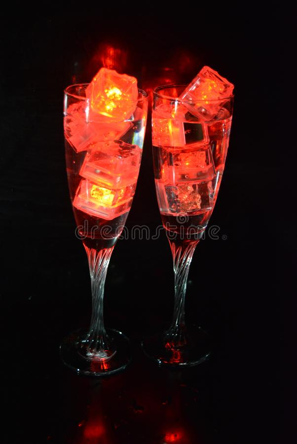 Two unusual glasses of champagne with a drink and bright red ice chips. Original image of love and mysticism in the form of two glasses of champagne with a red royalty free stock photos