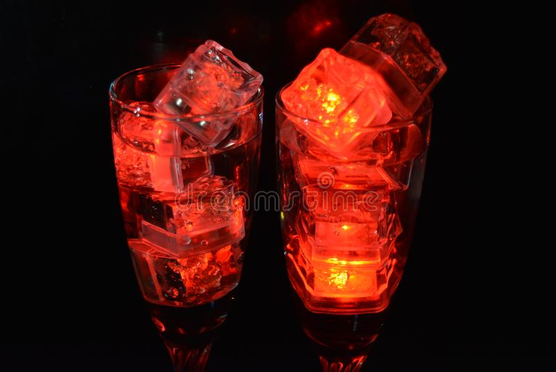 Two unusual glasses of champagne with a drink and bright red ice chips. Original image of love and mysticism in the form of two glasses of champagne with a red stock photo