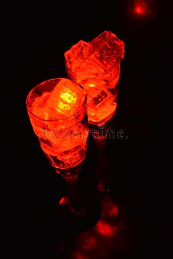 Two unusual glasses of champagne with a drink and bright red ice chips. Original image of love and mysticism in the form of two glasses of champagne with a red royalty free stock photography