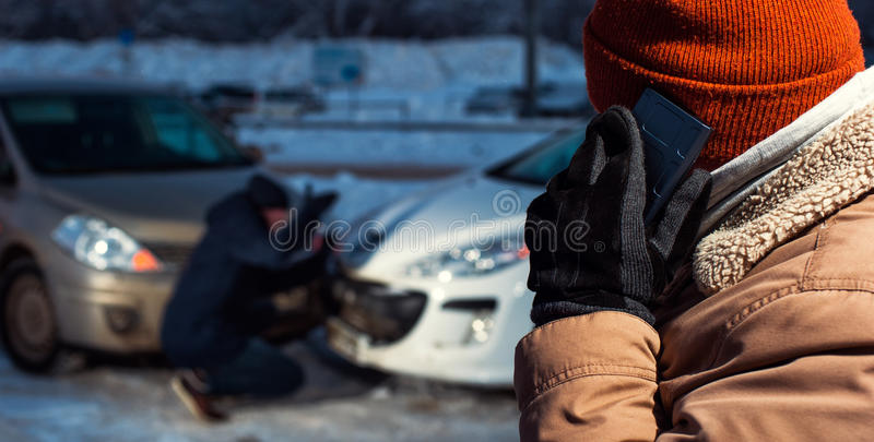 Two upset men on winter city street. Sad male driver calling to car assistance service after auto crash. Two upset men on winter city street. Car collision royalty free stock photography