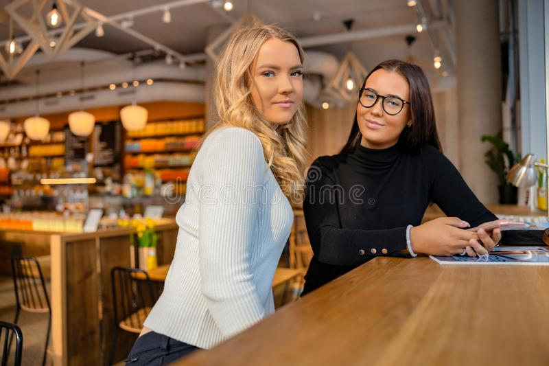 Two Urban Female Friends Looking At Camera in Cafe royalty free stock image