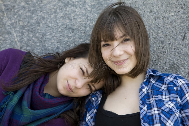 Two urban teen girls standing at wall. stock photography