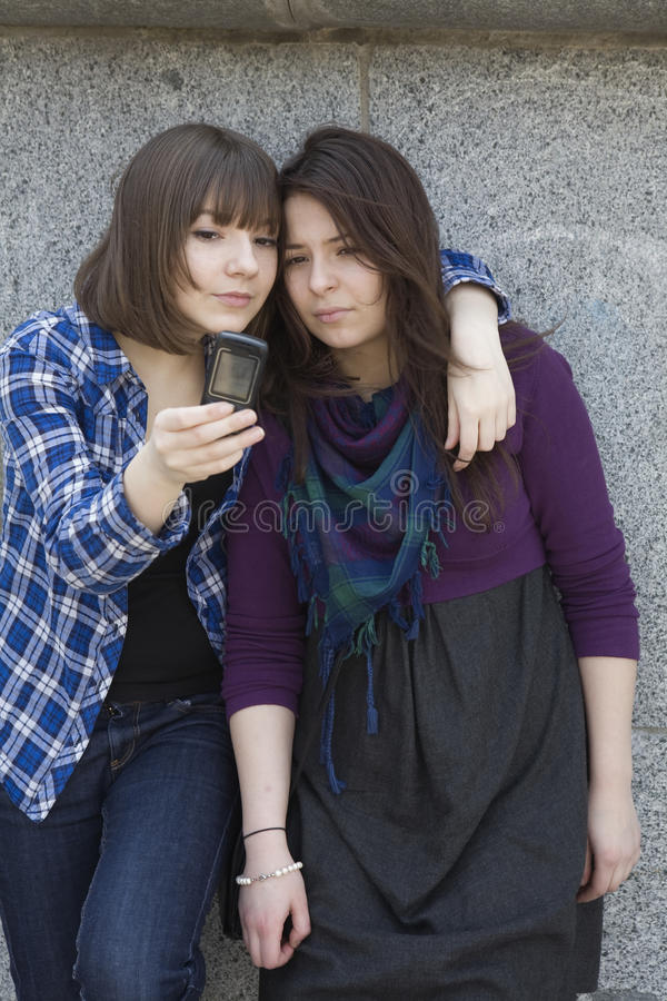 Two urban teen girls taking photo by mobile phone stock images