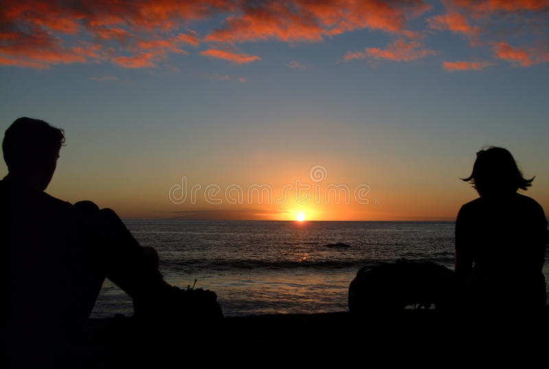 Two vacationers enjoy the sunset. Sunset through the silhouette of two vacationers, taken in La Gomera on the beach of Valle Gran Rey. Left of the sun the island royalty free stock photos