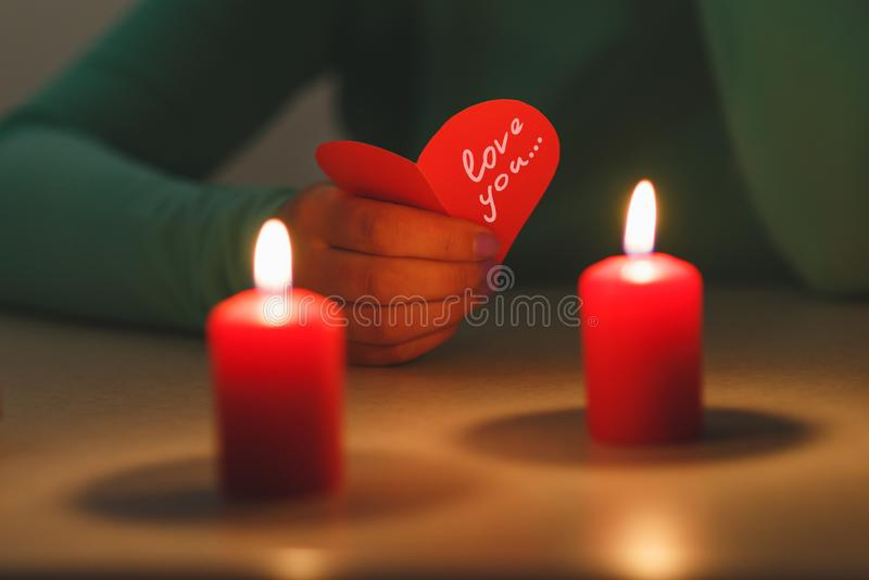 Two valentine hearts, burning candles, romantic atmosphere. Two Hearts on a wooden board. Valentine`s Day. Greeting card royalty free stock image