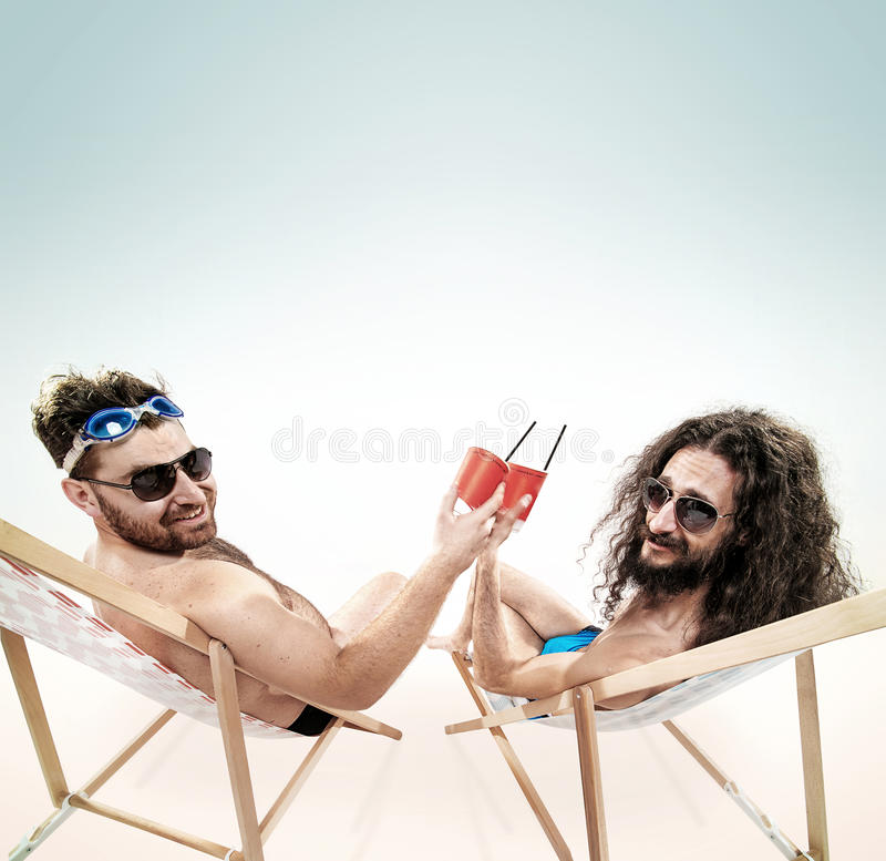 Two various guys resting together on the beach royalty free stock photos