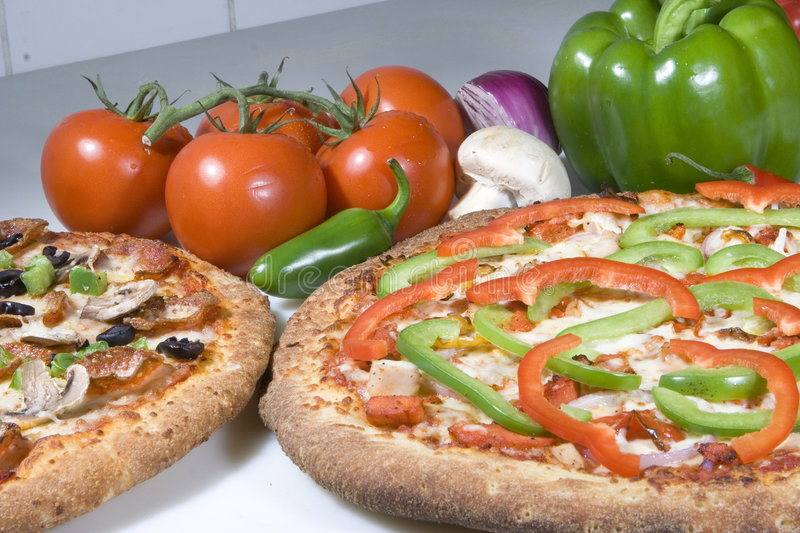 Two vegetarian pizzas. A closeup of two pizzas side by side on a table. They are topped with different vegetarian toppings. Tomatoes, mushrooms and capsicum have stock photography