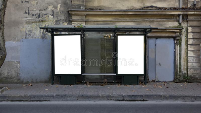 Two vertical blank white billboards at bus stop on old city street stock photography
