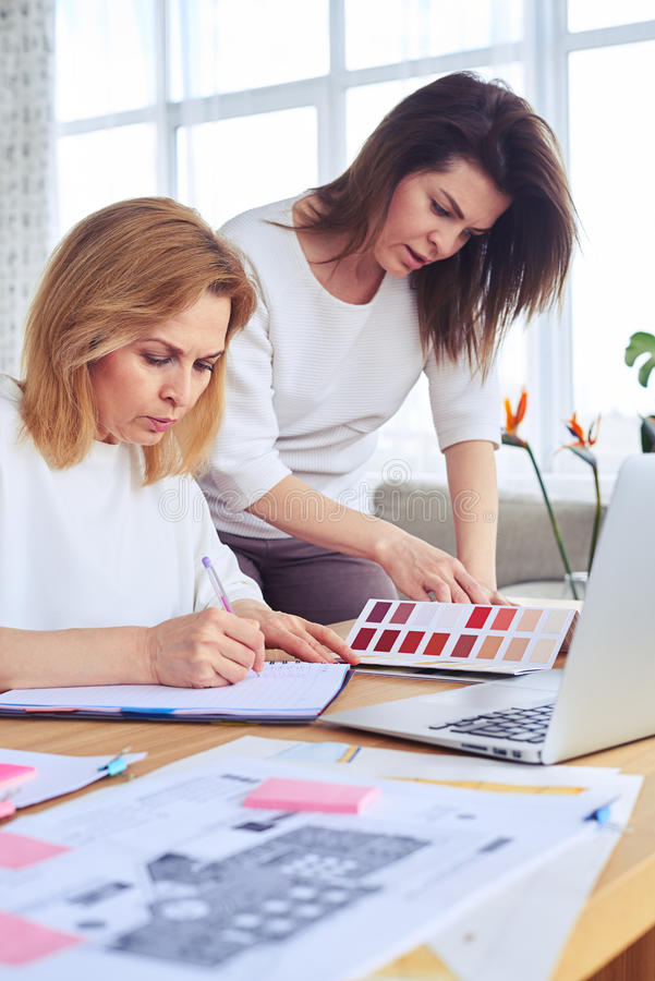 Download Two Very Serious Madams Looking Through Catalog Of Color Palette Stock Photo - Image: 92490812
