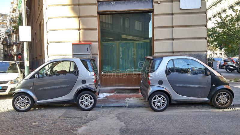 Two very small identical gray cars are parked in the same parking space in the city royalty free stock photos