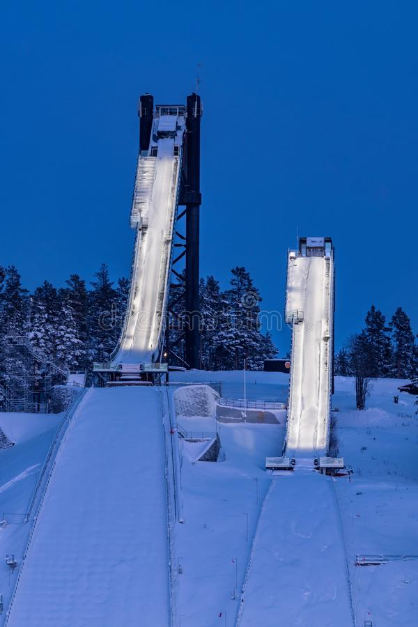 Two very tall ski jumping slopes or towers in Falun, Sweden. The two ski jumping slopes or towers with the below landing area at Lugnet stadium in Falun, Sweden royalty free stock photos