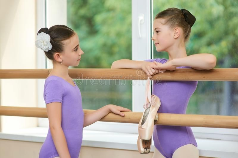 Two very young ballerinas having conversation. Beautiful young ballet dancers talking after dance rehearsal. Friendship and understanding between young people royalty free stock photos