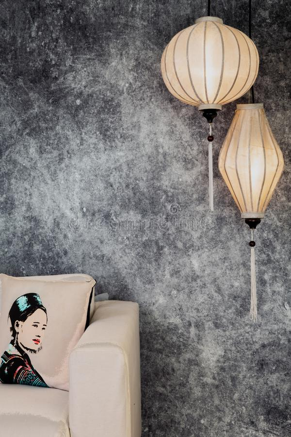 Vietnamese or Chinese white lanterns, spheric and oval, over vintage grunge concrete background with sofa and Vietnamese vintage stock photography