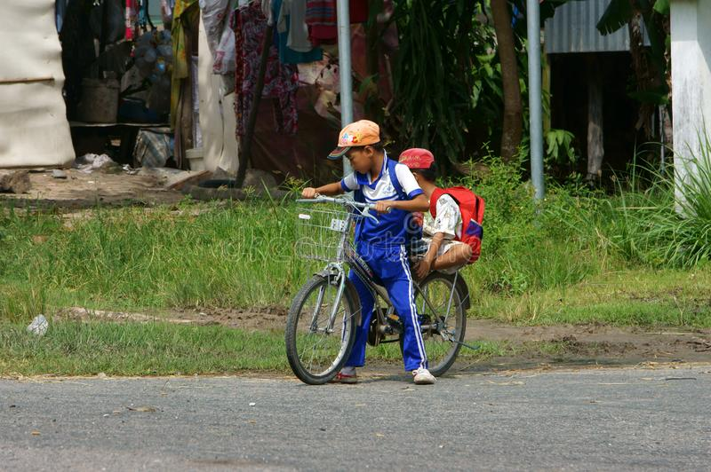Two Vietnamese little boy riding bike go to school. AN GIANG, VIET NAM- NOV 13, 2013: Two Vietnamese little boy riding bike go to school at noon, pupil in stock image