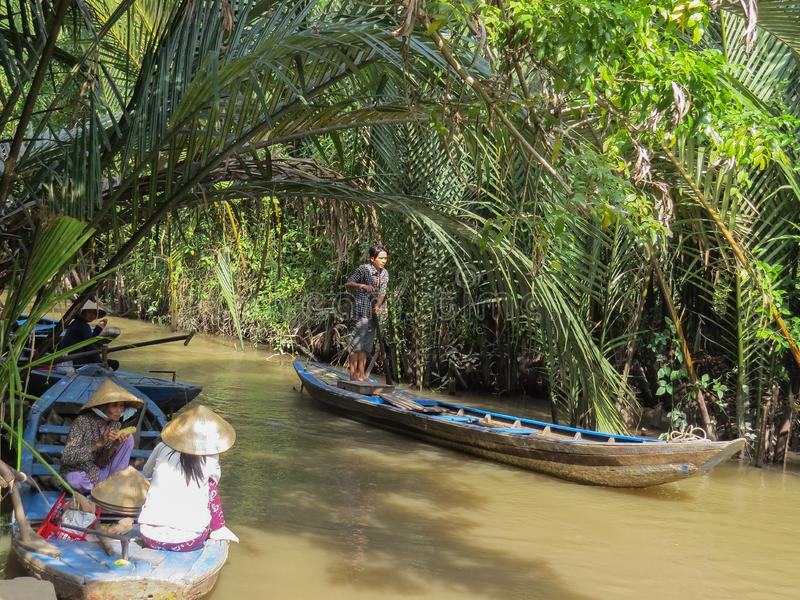 Two Vietnamese women have lunch sitting in a wooden boat. Standing on another boat and driving a paddle, a man moves stock image