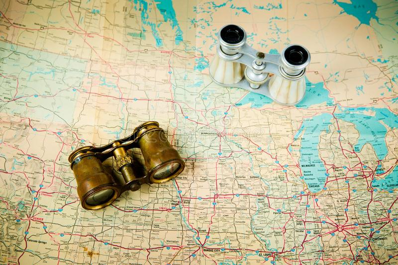 Two vintage binoculars on old map - brass metal body and silver stock image