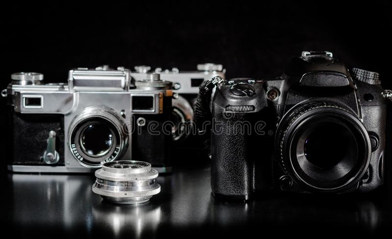 Two vintage cameras with lens and one modern camera on a black b stock photos