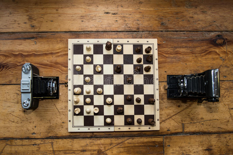 Two vintage cameras playing chess on a wooden board set on some royalty free stock photos
