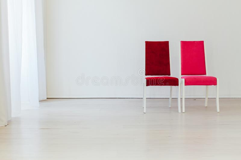 Two vintage chairs in the interior of an empty white room stock images