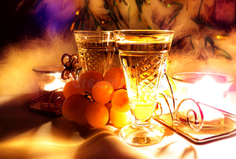 Two vintage champagne wineglass festive evening candle and gentle sweet green grapes. stock photo