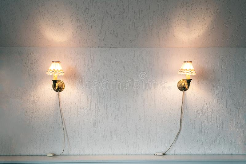Two vintage lamps on the wallpaper . Wall light of gilded metal with two electric candles stock photography
