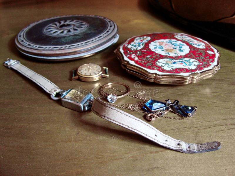 Two vintage puff boxes, two vintage female watches, ring and neckless. Nostalgia. Memories. Family jewelry. Poignant. stock photo