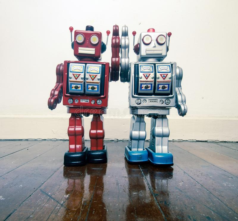 Two vintage robot toy happy together on a wooden floor royalty free stock images