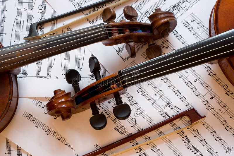 Two violins with bows on sheet music. Two violins with bows lauing on sheet music stock image