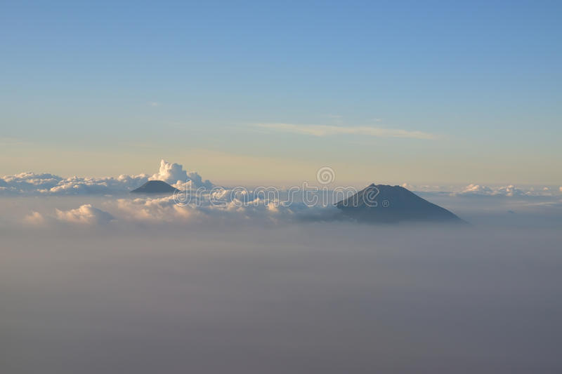 Two volcano mountains visible above the cloud around Yogyakarta, Indonesia near sunset. The silky surface beautiful clouds sometimes gave the impression that royalty free stock images