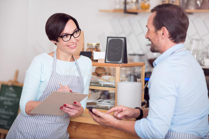 Two waiters in aprons working in cafe. Team spirit. Merry and positive cafe workers discussing something while holding folder and using smart phone stock photography