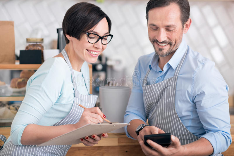 Two waiters communicating in cafe. Friendly colleagues. Happy and smiling cafe workers holding folder and using smart phone royalty free stock photography
